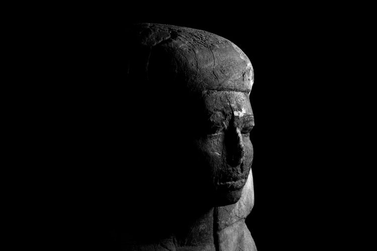 The head from a carved ancient Egyptian wooden coffin