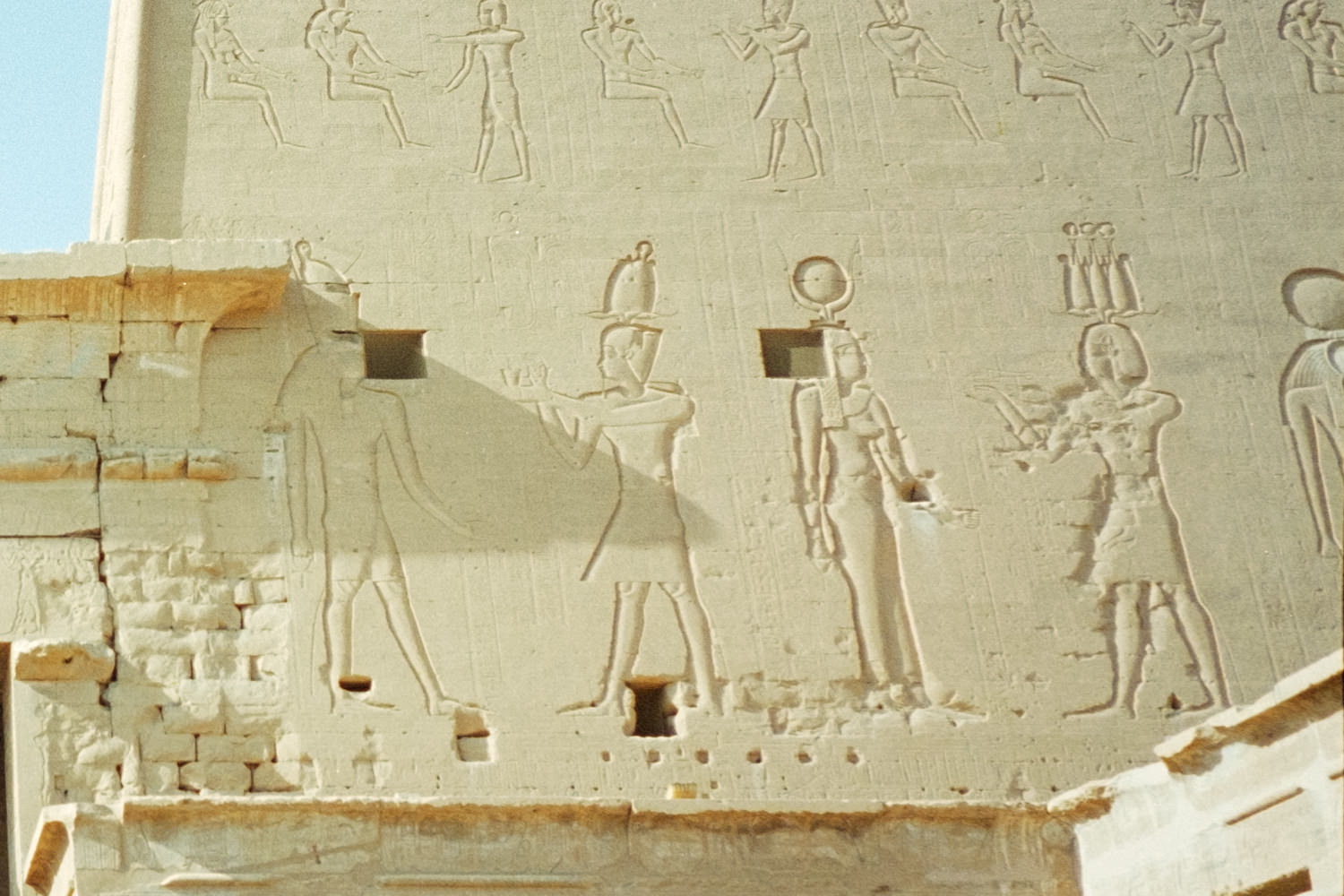 A close-up of carvings on the walls of Edfu temple showing various deities and pharaohs, including Isis