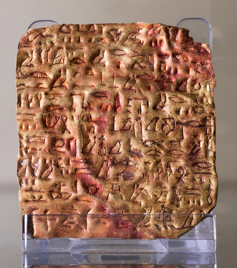 A small, gold ancient Egyptian plaque inscribed with hieroglyphs