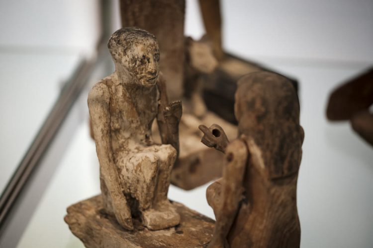 Two ancient Egyptian tomb model people, a man and a woman, sitting facing each other