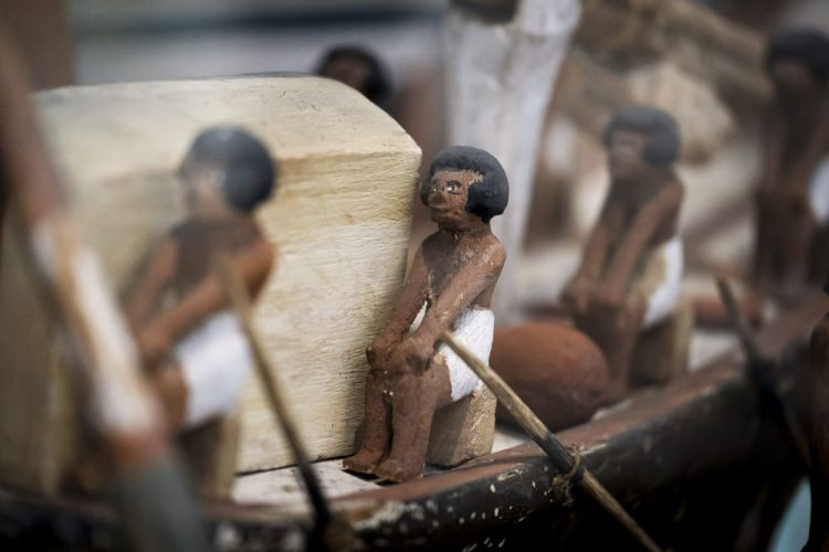 An ancient Egyptian wooden model ship with sailors sitting along the side with oars