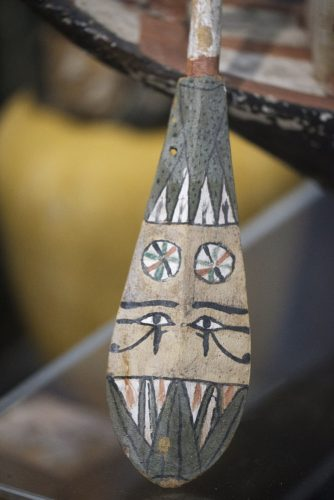 A small, ancient Egyptian model oar painted with eyes and plant decorations