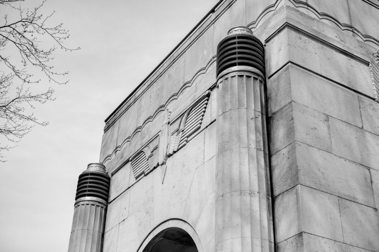An art deco-style building with Egyptian Revival columns and winged emblem