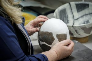 A conservator repairing an ancient Egyptian pot