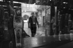 A reflection of a visitor to the Egyptian gallery at Bristol Museum