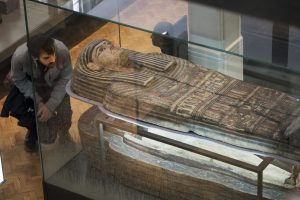 A man looking at an Egyptian mummy at the Manchester Museum