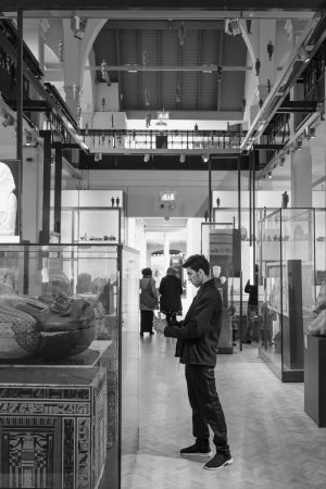 A man taking a photo of an Egyptian coffin at the Manchester Museum