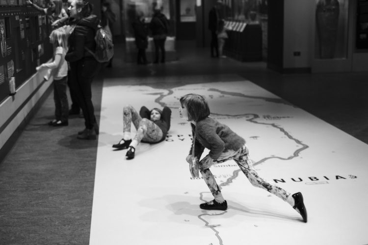 Two girls playing in the Egyptian gallery at the World museum