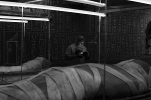 A man looking at his phone in the Egyptian mummy room at the World Museum