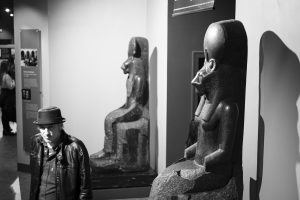 A man next to two statues of the Egyptian goddess Sekhmet at the world museum
