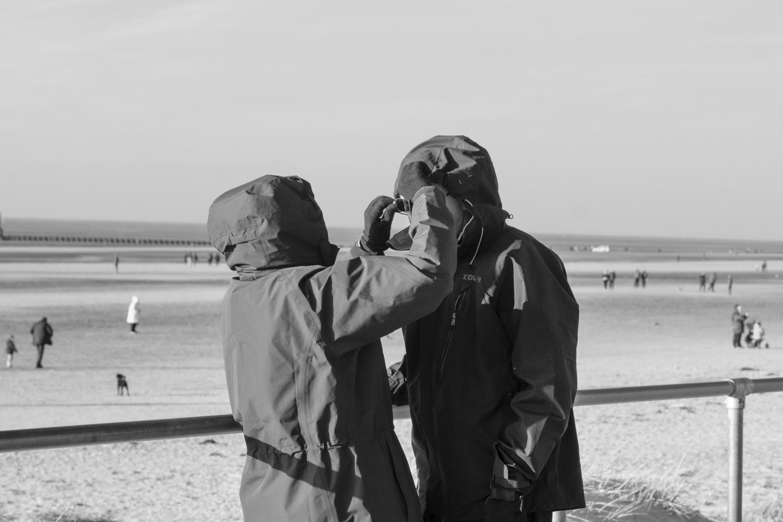 a woman adjusting the hood on a man's jacket