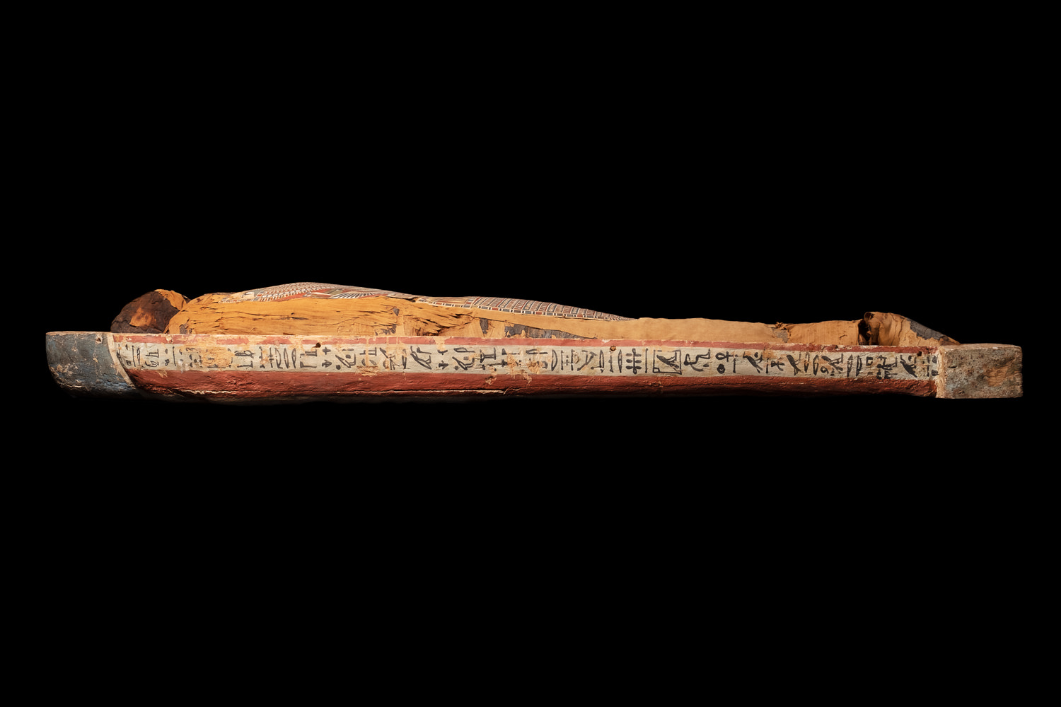 the side of an ancient egyptian wooden coffin and wrapped mummy