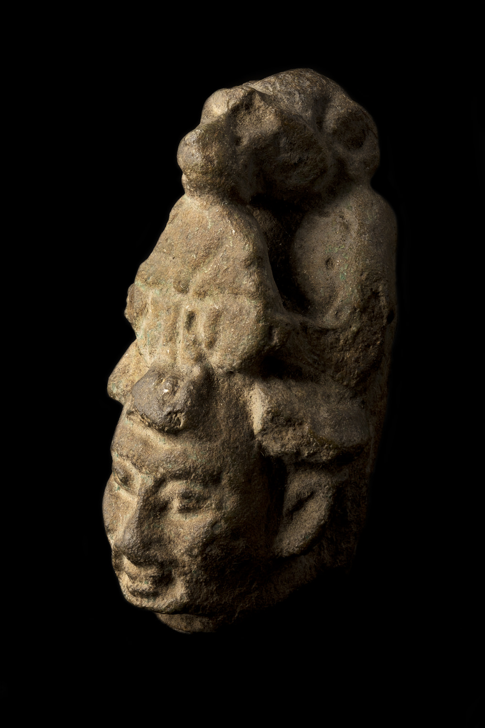 a small, stone egyptian statue of a head with a baboon at the back
