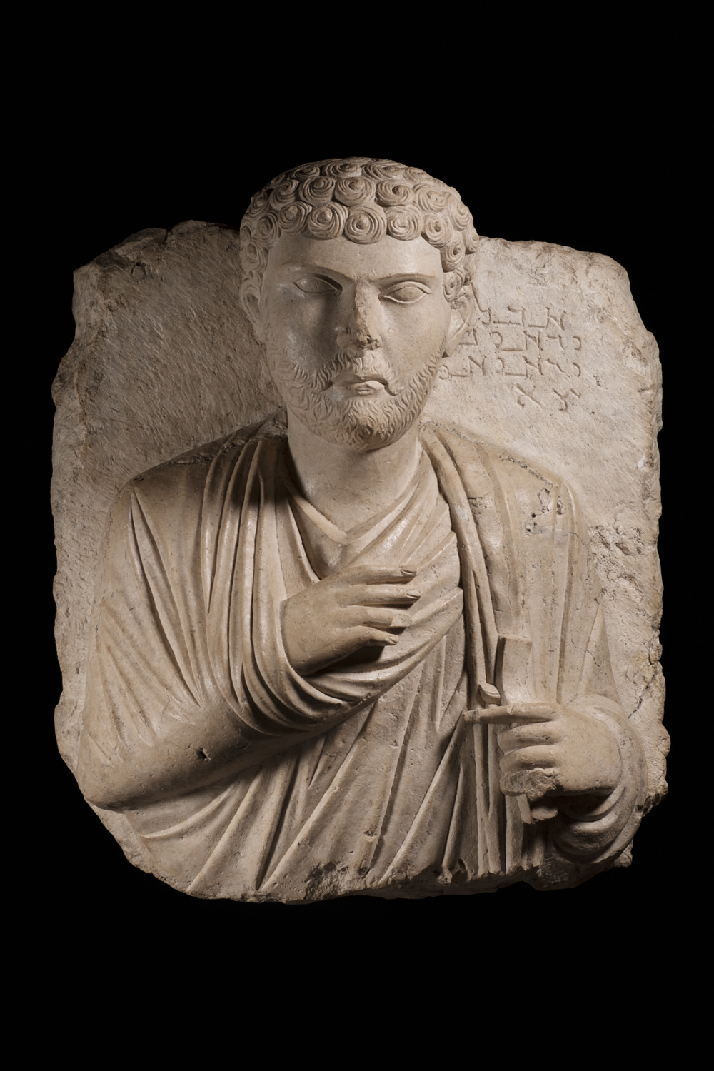 a limestone bust of a man in greco-roman clothes
