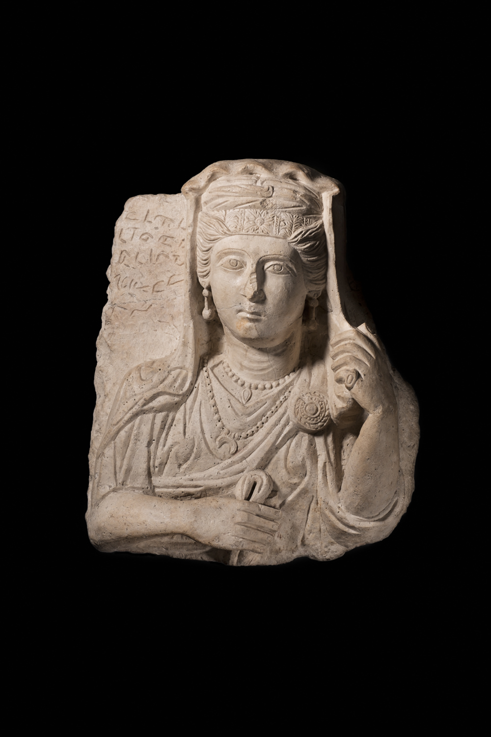 a limestone bust of a woman in greco-roman clothes