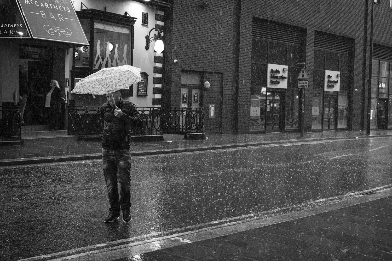 a man in the rain under a broken umbrella